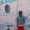 somaliland – boy posing in front of their wall of football fame, burao, somaliland